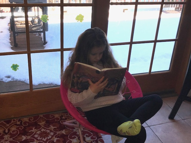 After playing a full day outside in the snow, some children headed indoors where it was nice and warm. This student is relaxing in a favorite spider chair and reading a Harry Potter book by J.K. Rowling.