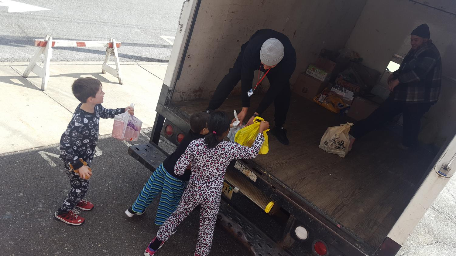 Third graders from Christina Knaack's homeroom help load canned goods onto the donation truck. The truck delivers the items to local food pantries.