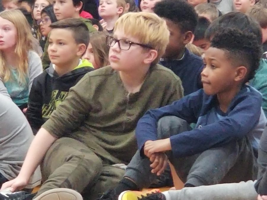 Students in third and fourth grade attentively listen as their peers perform on stage. Winter Concert rehearsal is a highlight of the week for many students.
