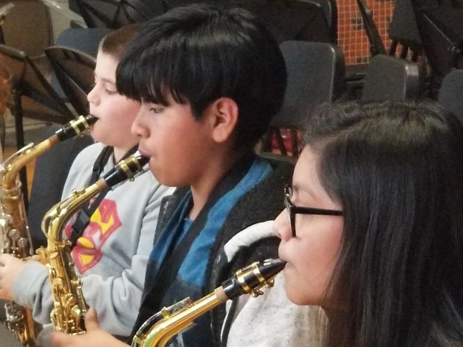 These students are playing woodwind instruments. Specifically, the alto saxophone involves blowing air into a mouthpiece which manes a reed move back and forth.