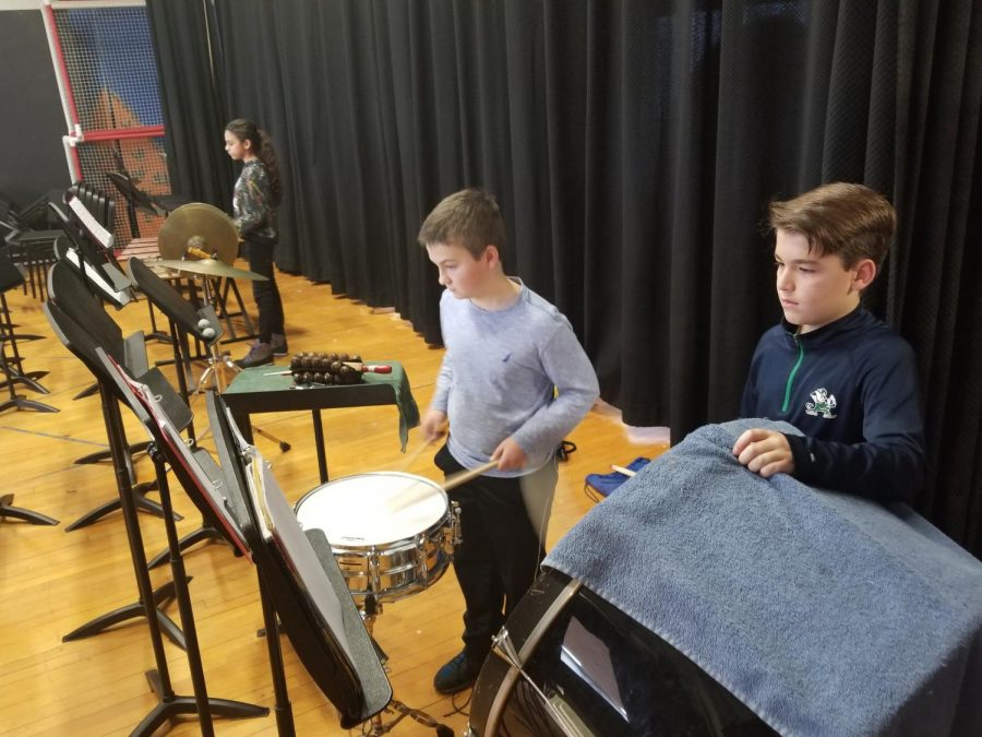 At the top of the photo, a student is playing the marimba. The marimba is a percussion instrument because it makes a sound when struck.