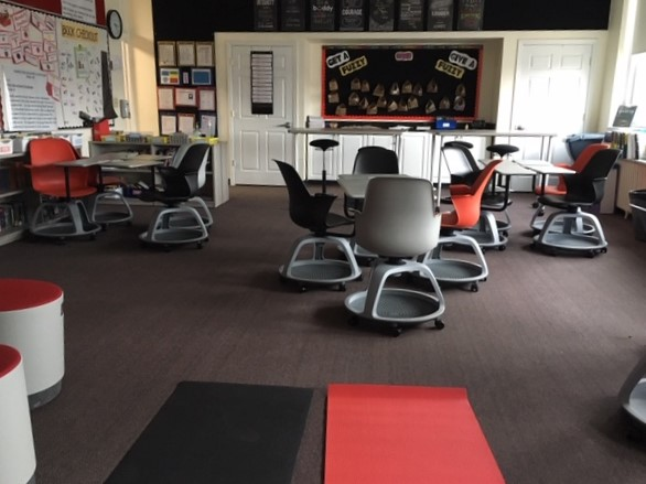 This sixth-grade Language Arts classroom has yoga mats, rolling chairs, and standing desks. Many students find that movement helps them concentrate on their studies.