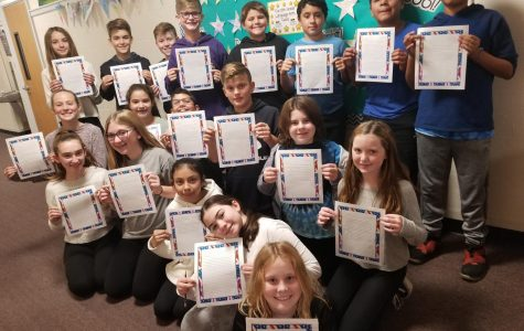 Sixth grade students voted to write letters of repsect to various community members as their Week of Respect yearlong project. These students from Mrs. April Catuogno's class display their letters to military men and women written in the month of November.