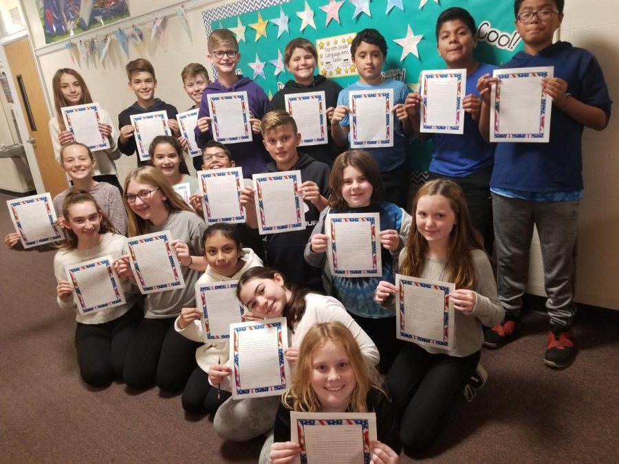 Sixth+grade+students+voted+to+write+letters+of+repsect+to+various+community+members+as+their+Week+of+Respect+yearlong+project.+These+students+from+Mrs.+April+Catuogno%27s+class+display+their+letters+to+military+men+and+women+written+in+the+month+of+November.