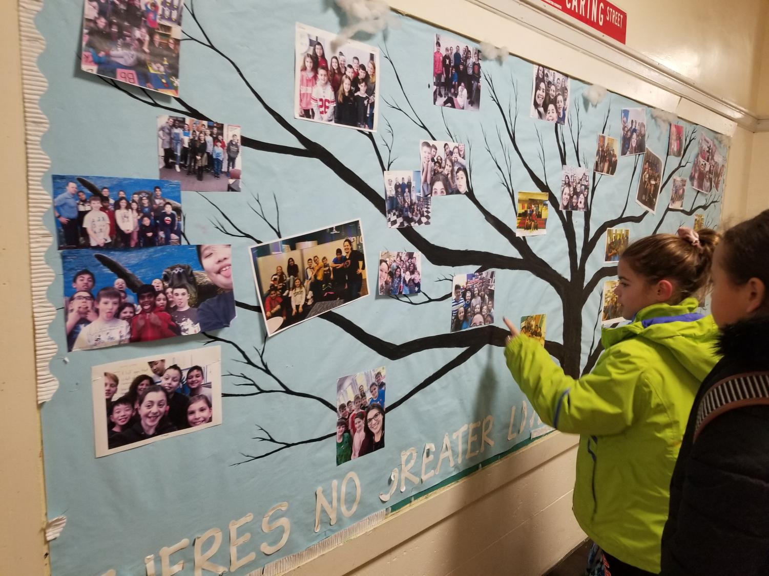 This bulletin board outside the Learning Lab hosts photos of thirty different school families at school, There is one family for each staff member.