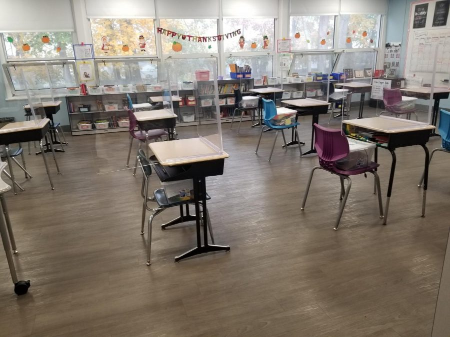Students who opted for on-site instruction are six-feet apart in desks surrounded by Plexiglass on three sides. All students and staff wear masks.