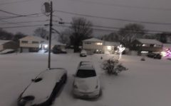 As the snow falls, it covers  the cars and roads.